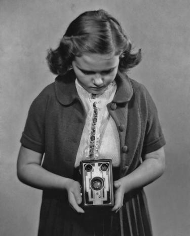 A girl taking a photograph with a Kodak box Brownie camera.