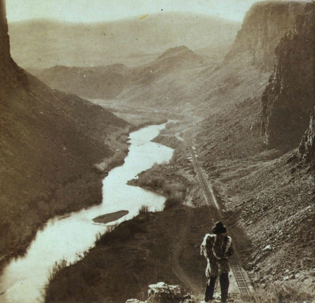 A native American man overlooking the newly completed transcontinental railroad in Nevada, c.1868